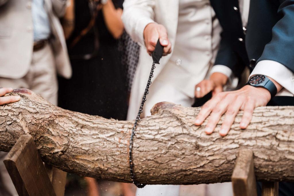 Ein Paar bei einer Hochzeit zersägt traditionell einen Baumstamm