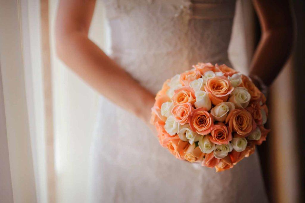Runder Brautstrauß mit orangen und weißen Rosen
