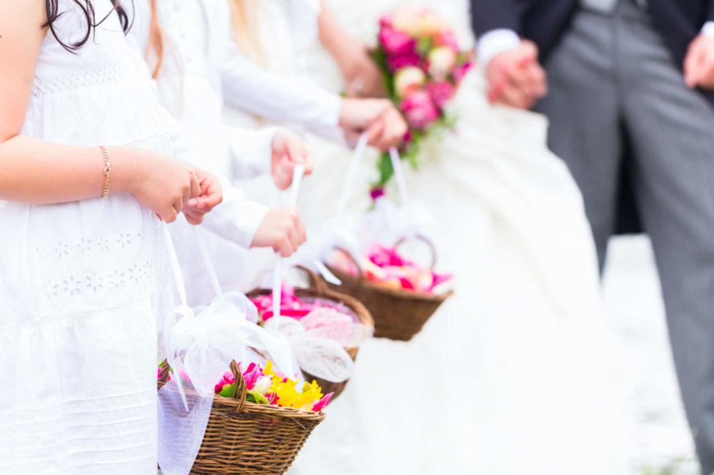 Blumenkinder mit Körben voller Blumen bei einer Hochzeit