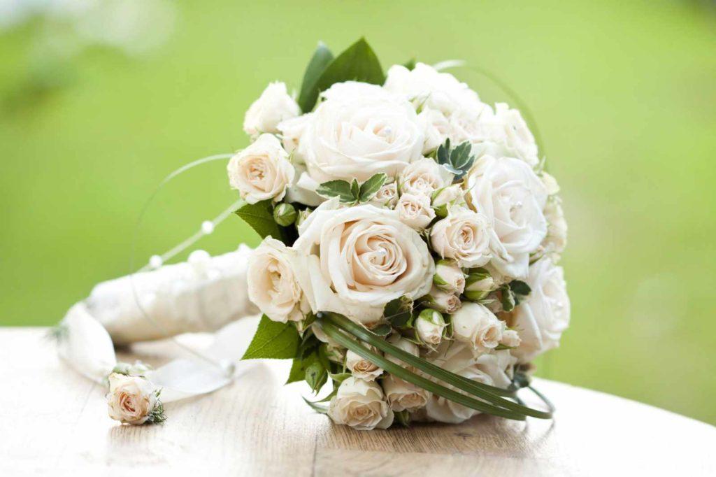 Ganz in Weiß, mit einem Blumenstrauß