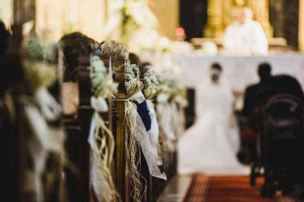 Paar in der Kirche bei einer Trauzeremonie. Fürbitten werden von Freunden und Verwandten vorgetragen.