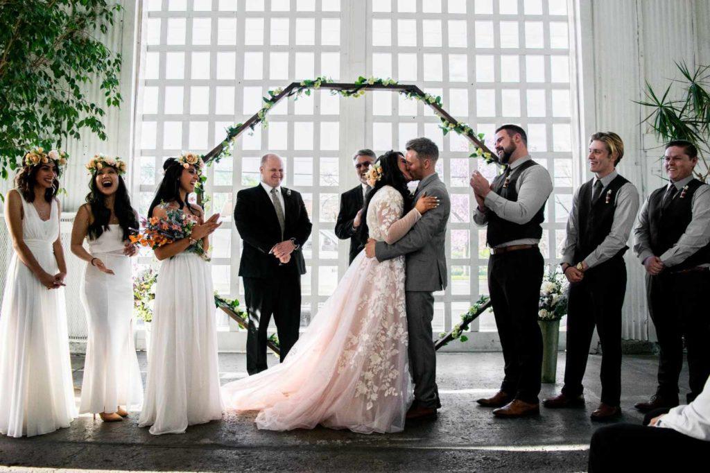 Ein Brautpaar hat gerade JA gesagt und darf sich küssen. Umringt von Trauzeugen und Trauzeuginnen. Wer sich die schönsten Hochzeitsdaten für 2022 sichern will, sollte jetzt mit der Planung beginnen.