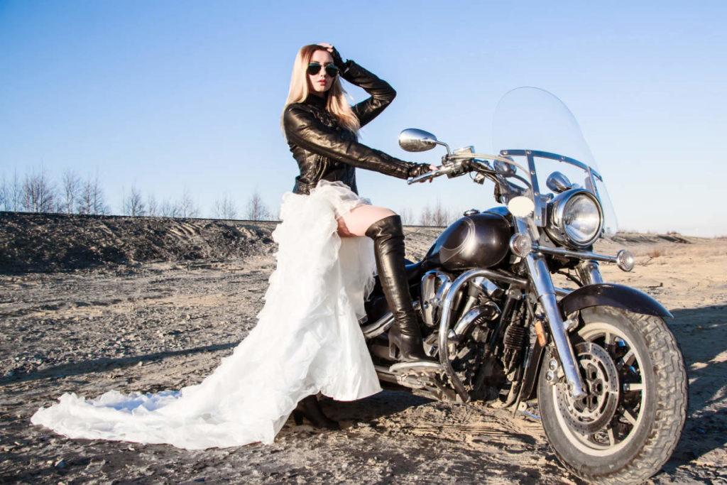 Braut mit Lederjacke und Harley Davison bei einer Biker Hochzeit