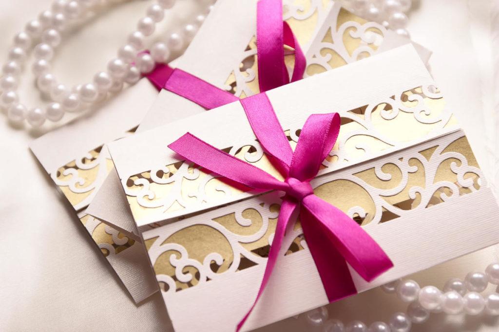 Einladungskarten für eine Hochzeit mit Gold und einer lila Schleife