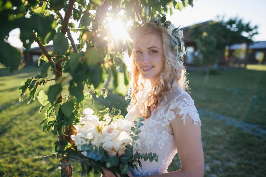 Braut unter einem Baum mit weißen Blumen. Die Braufrisur ist geflochten und sie hat weiße Rosen im Haar. Die Hochzeit findet auf einem Bauernhof statt und die Sonne ist gerade am Untergehen. Unser Leitmotiv zum Ratgeber Brautfrisuren