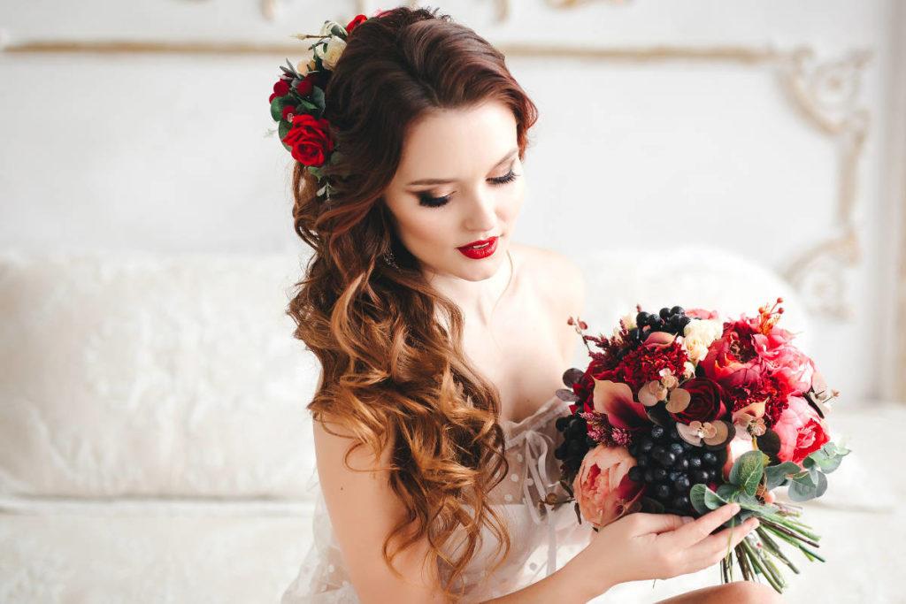 Braut im Halbprofil mit Brautfrisur und gelockten Haaren. Der Blumenschmuck in der Brautfrisur ist passend zu dem Brautstrauß, den Sie in der Hand hält.