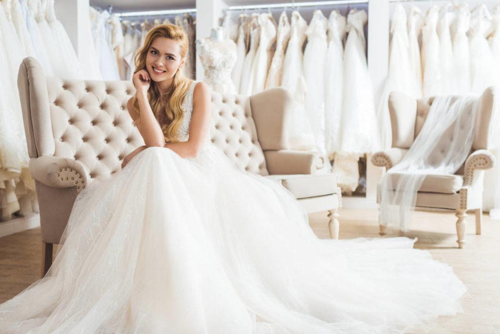 Eine junge Braut sitzt auf einem Sofa und probiert ein Brautkleid an. Im Hintergrund hängen viele weitere Brautkleider an Stangen. Die Atmosphäre ist entspannt, da sie einen Termin gemacht hat und sich die Verkäuferinnen für sie Zeit nehmen.