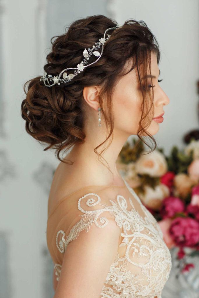 Braut von der Seite mit lockerer Hochsteckfrisur und Haarschmuck