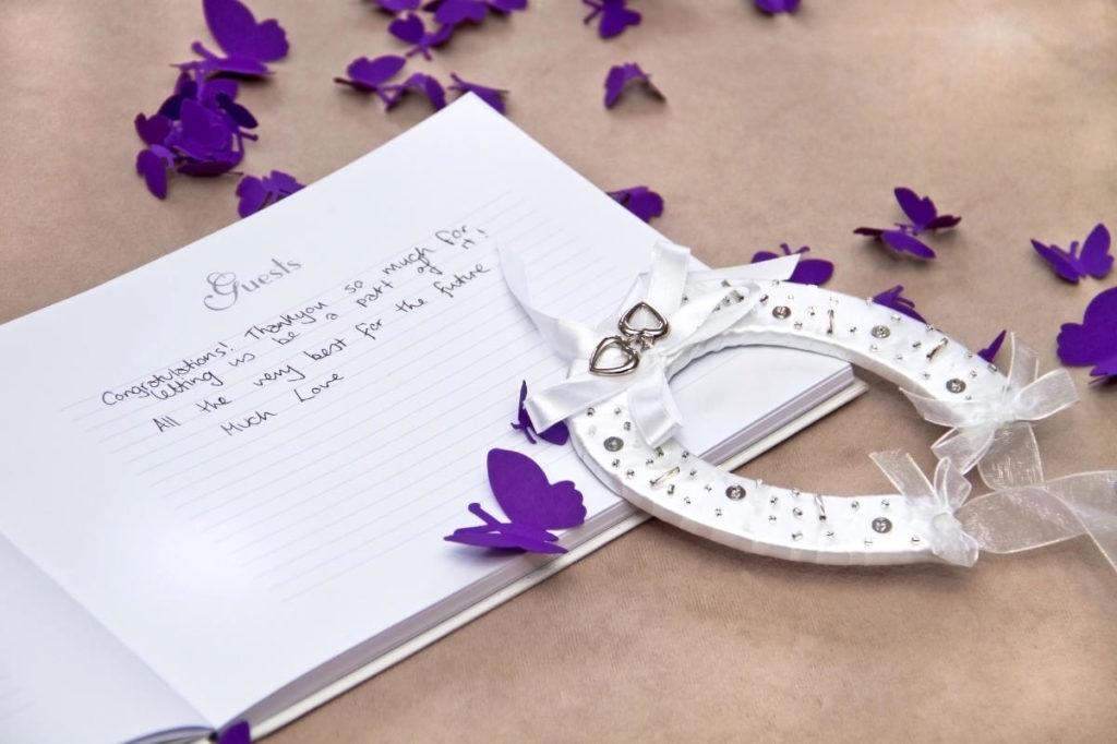 Offenes Gästebuch in dem jeder seinen Wunsch für das Brautpaar eintragen kann. Mit Hufeisen und lila Papierschmetterlingen dekoriert