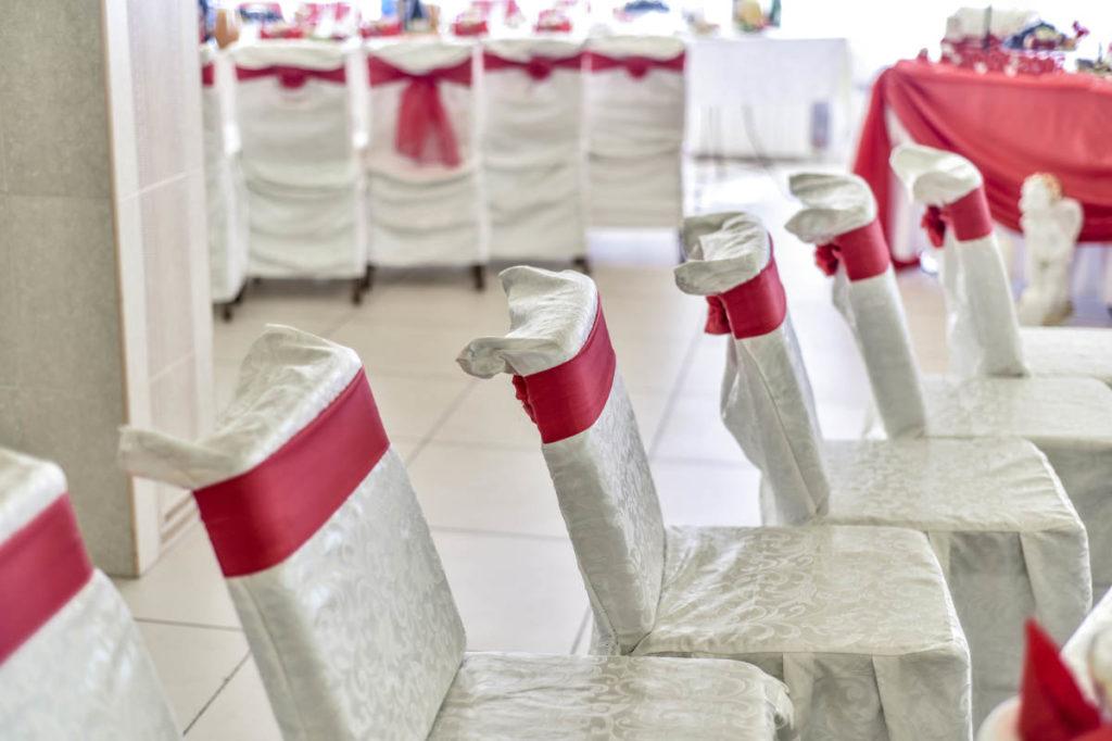 Weiße Stühle mit roter Schärpe warten darauf besessen zu werden.