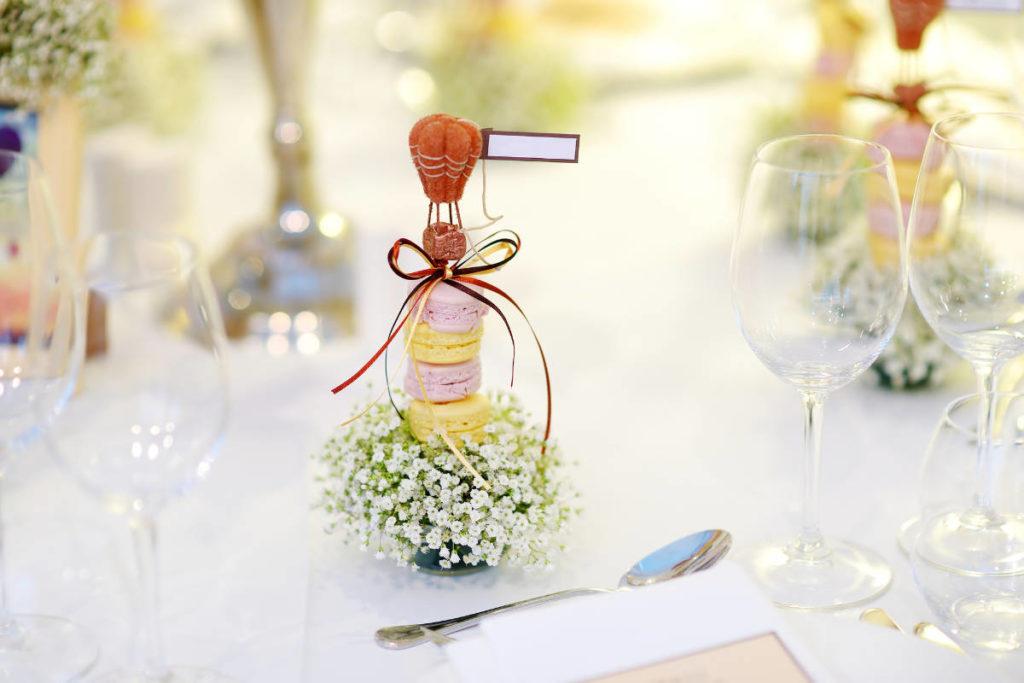 Essbare Tischkarte: Ein Turm aus Macarons mit Blumen als Namenskarte auf einem Tisch.
