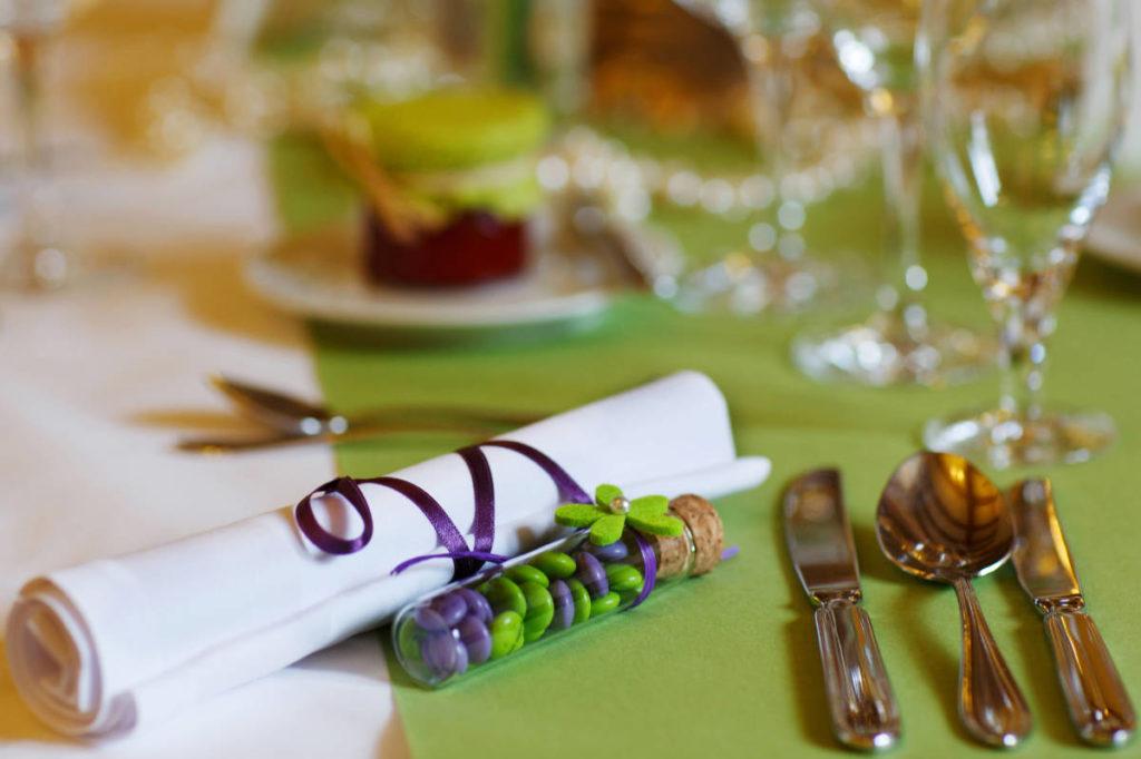 Reagenzglas mit bunten Schokolinsen gefüllt auf einem Tisch. Dekoelement als Namens- oder Tischkarte