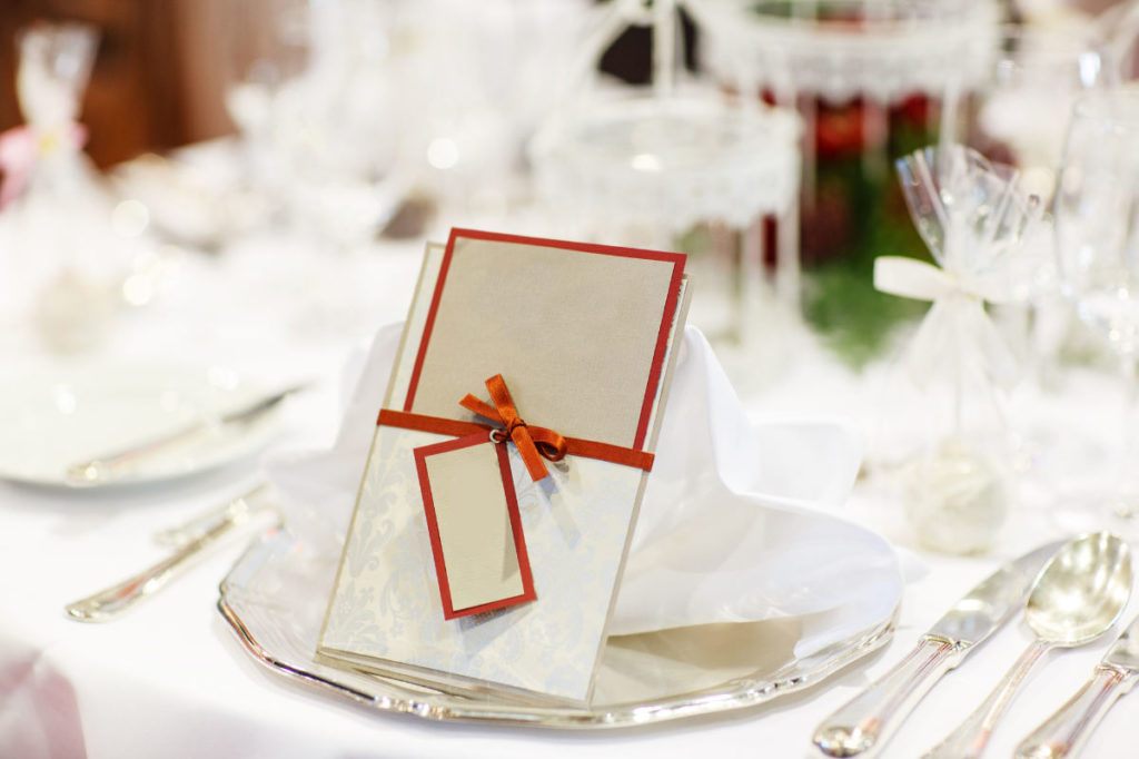 Tischdeko auf einer Hochzeit. Auf dem Teller liegt ein Gastgeschenk in Gutscheinform.