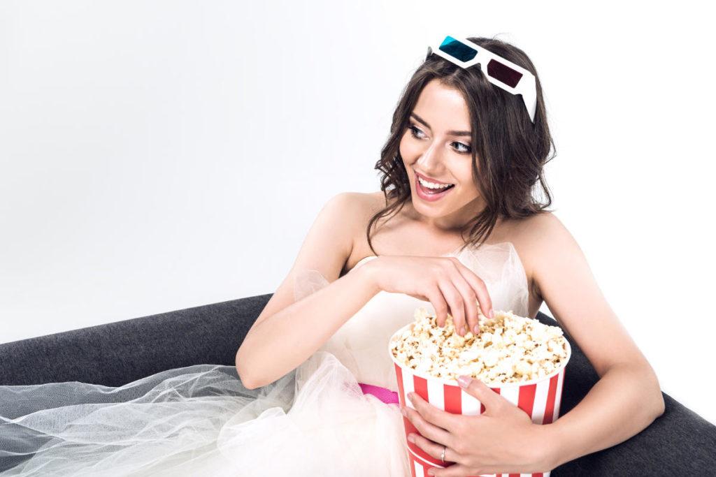 Die besten Hochzeitsfilme schaut man als Braut mit Popkorn auf einem Sofa sitzend.