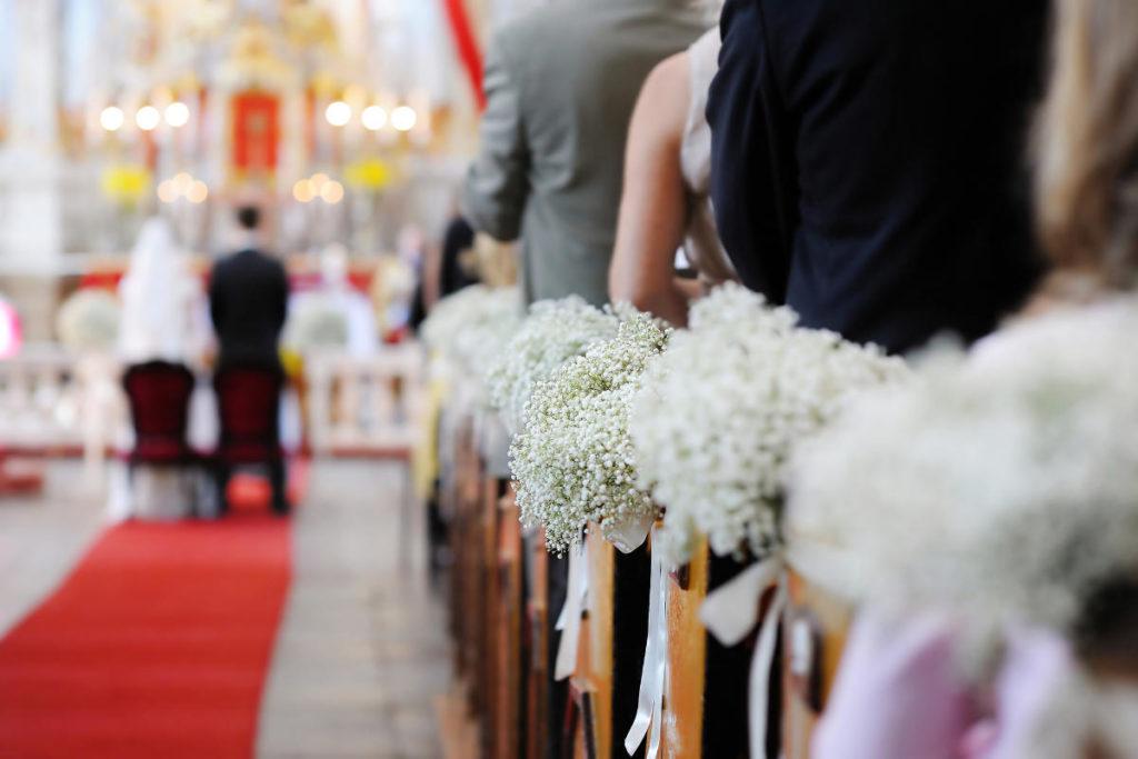 Ein Blick in den Gang einer Kirche bei einer Hochzeit. Die Bänke sind mit Schlierkraut dekoriert.