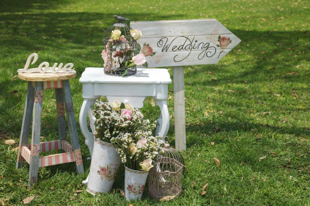 """Ein Wegweiser mit Aufschrift """"wedding"""" zusammen mit einiger Hochzeitsdeko"""