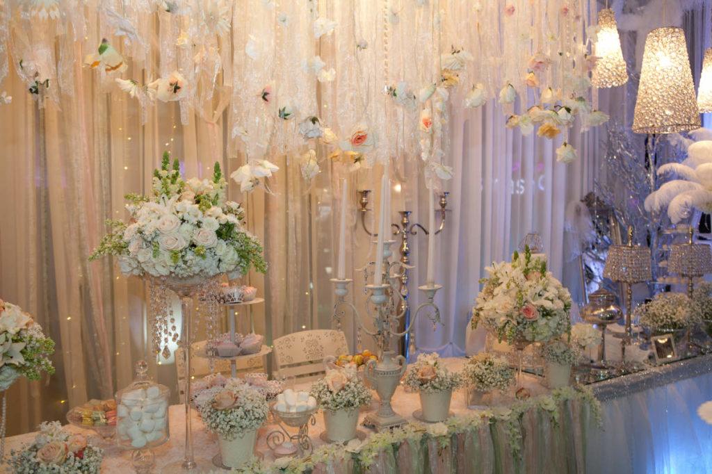 verspielte Tischdeko bei einer Hochzeit mit einer Vielzahl von Dekoelementen und Glitzerlampen.