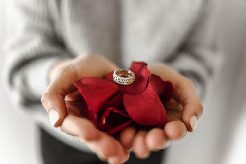 Ein edler Ring wird als Hochzeitsgeschenk auf ein paar Rosenblättern angereicht.