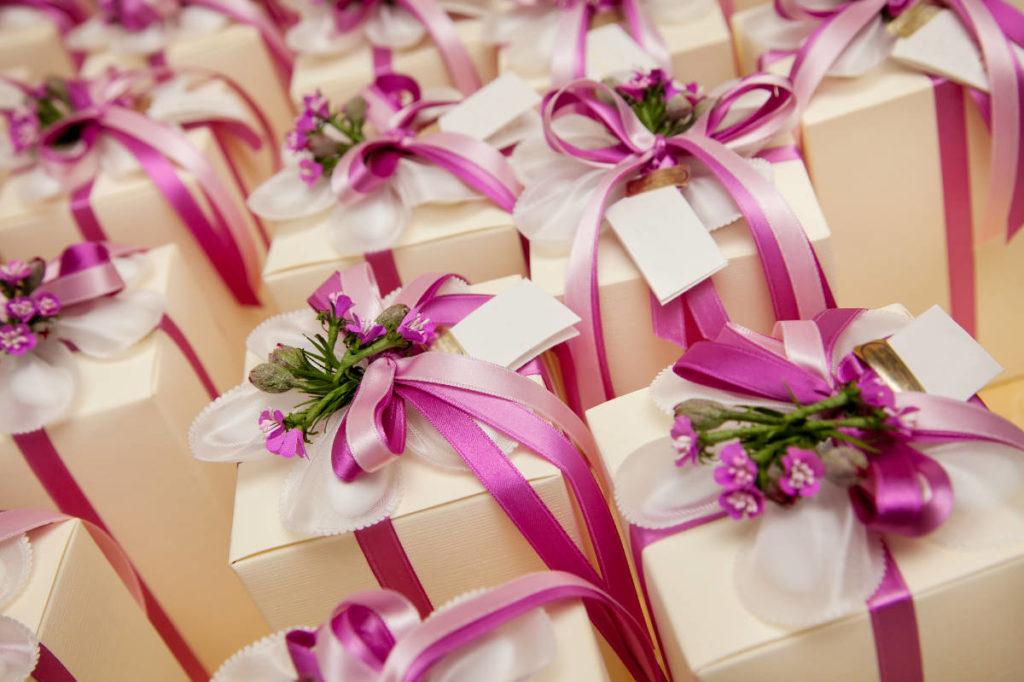 viele kleine Hochzeitsgeschenke mit lila Schleifen und Blüten dekoriert