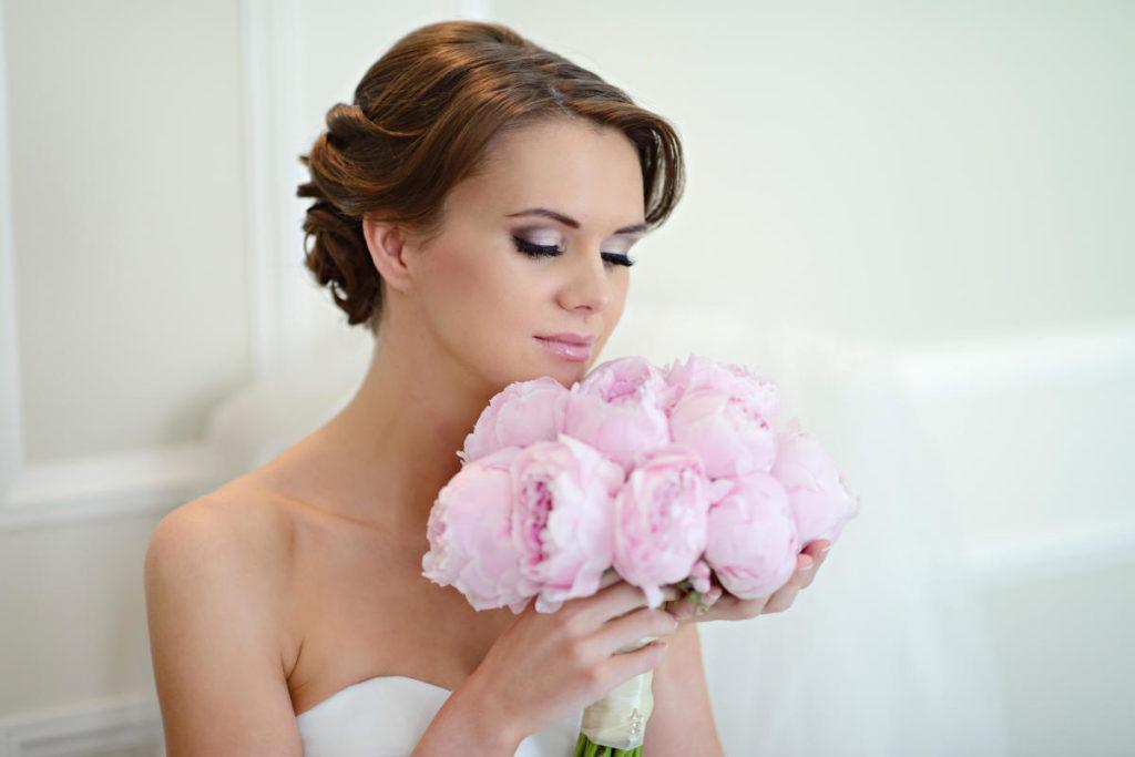 Hübsche Braut mit rosa Pfingstrosen. Sie schnüffelt daran und trägt eine Brautfrisur für kurze Haare