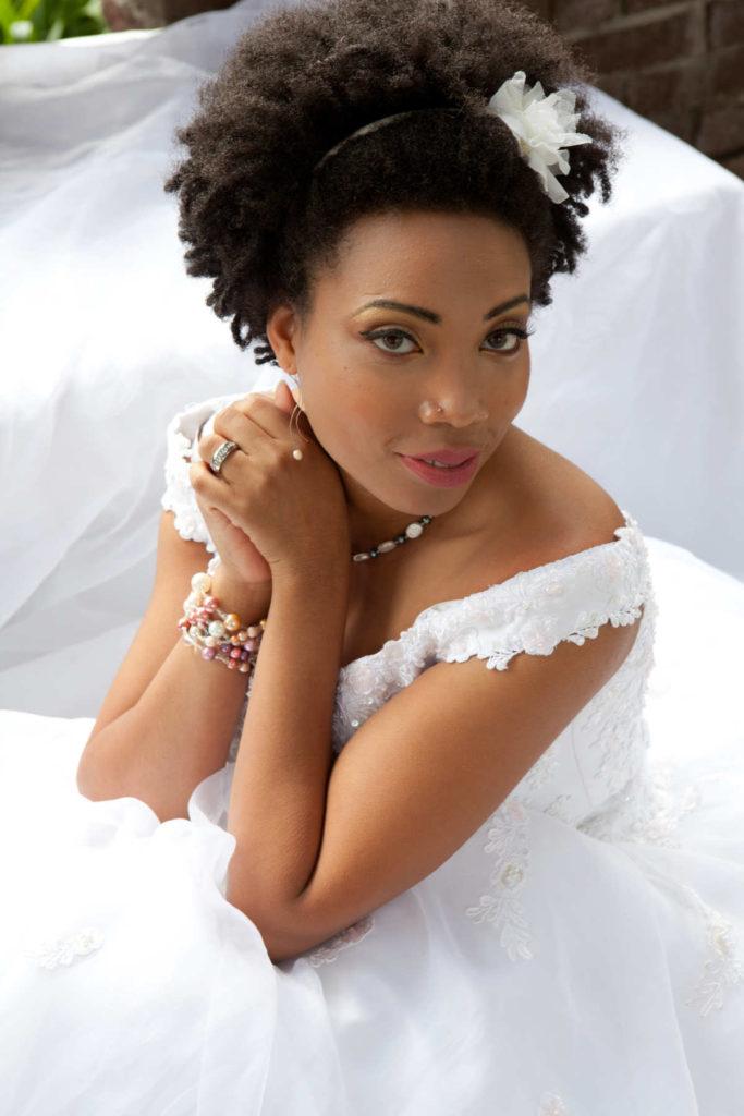 Eine Braut schaut seitlich in die Kamera. Ihre Hände sind gefaltet und die Braufrisur kurze Haare.