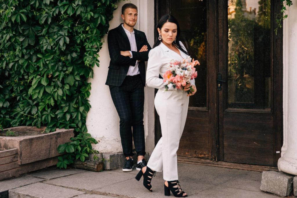 Eine moderne Braut mit einem Hosenanzug steht vor dem Eingang eines Standesamts