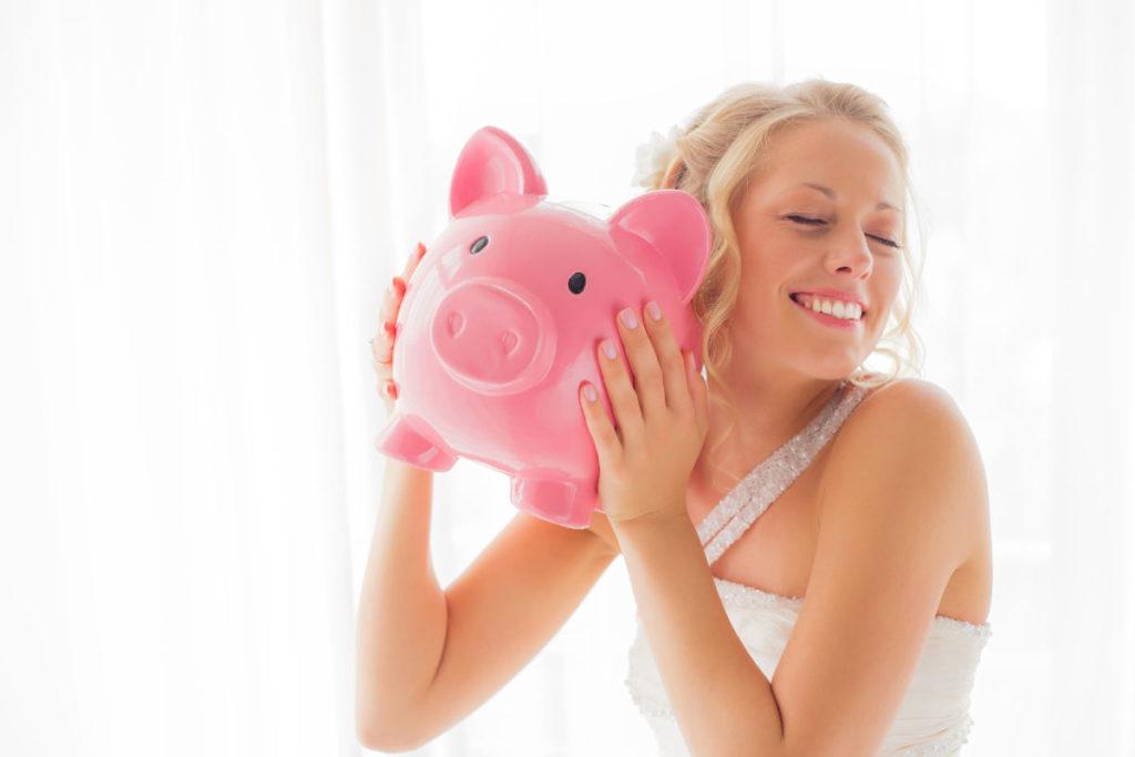Eine Braut hält ein rosa Sparschwein hoch. Unser Titelbild zu unserem Ratgeber Geldgeschenk - Hochzeit