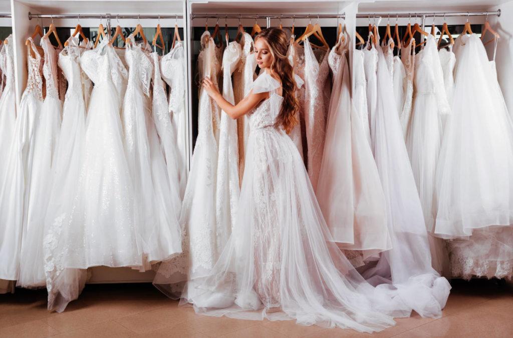 Eine Braut steht in einem Brautmodengeschäft und probiert Kleider an