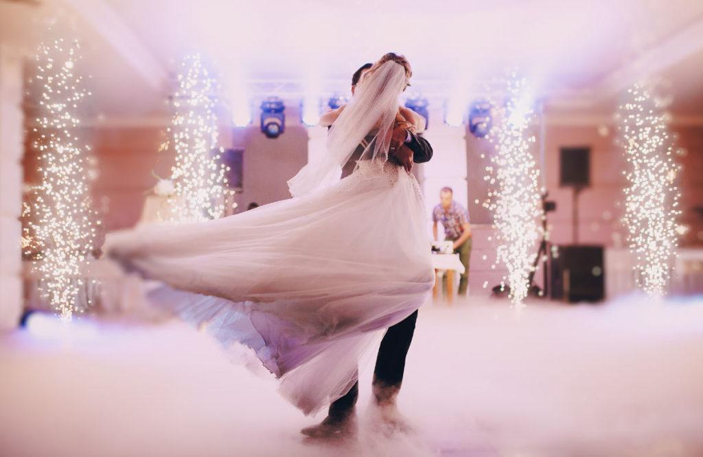 EinBrautpaar auf einer Tanzfläche. Der Boden ist mit Nebel eingehüllt und am Rand der Tanzfläche ist Feuerwerk.