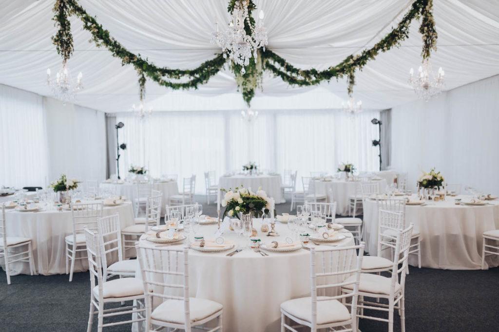 Klassisch herrscht bei Hochzeiten natürlich immer die Farbei weiß vor. Auf dem Bild ist eine Hochzeitsraum mit Stühlen, Tischen und Deckenvorhängen ganz in weißer und cremefarbener Hochzeitsdeko gehalten. Grüne Blumenkränze geben Farbtupfer.