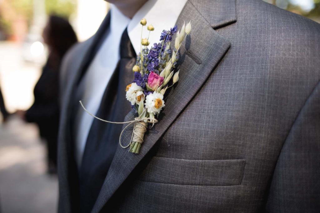 Nahaufnahmen von einem Bräutigam mit Krawatte und Blumenschmuck am Revers