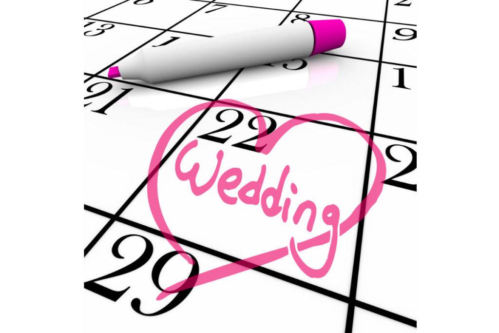 Ein Kalender auf dem ein Hochzeitsdatum am 22 mit einem rosa Herz und dem englischen Wort Wedding für Hochzeit markiert ist.