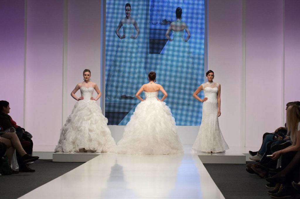 Drei Bräute auf einer Brautmodenschau gehen auf dem Laufsteg