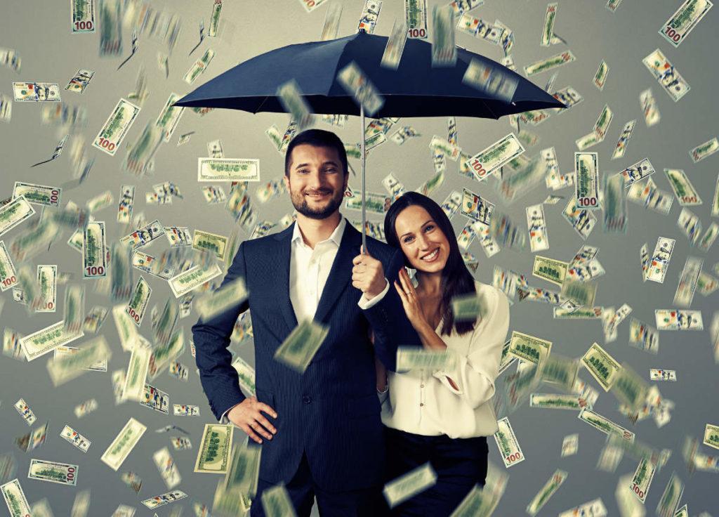 wer zahlt was bei der Hochzeit - Ein Brautpaar unter einem Regenschirm. Es regnen Geldscheine