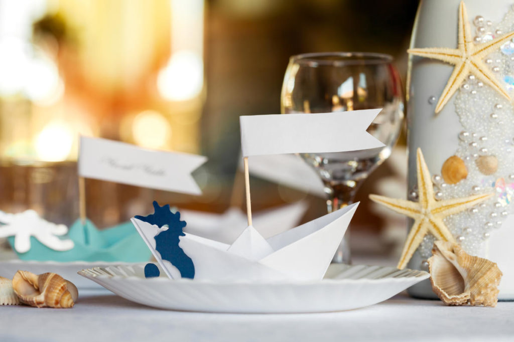 Papier Segelschiffchen als Namenschilder auf einem gedeckten Tisch