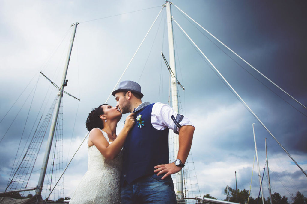 Brautpaar küssend vor einem Segelschiff und bewölktem Himmel. Unser Beitrag zu Hochzeitsdeko maritim