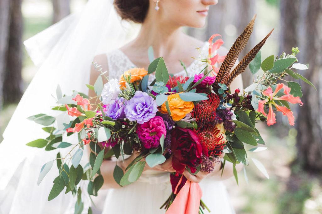 Ein großer Blumenstrauß im Boho Stil wird von einer Braut gehalten.