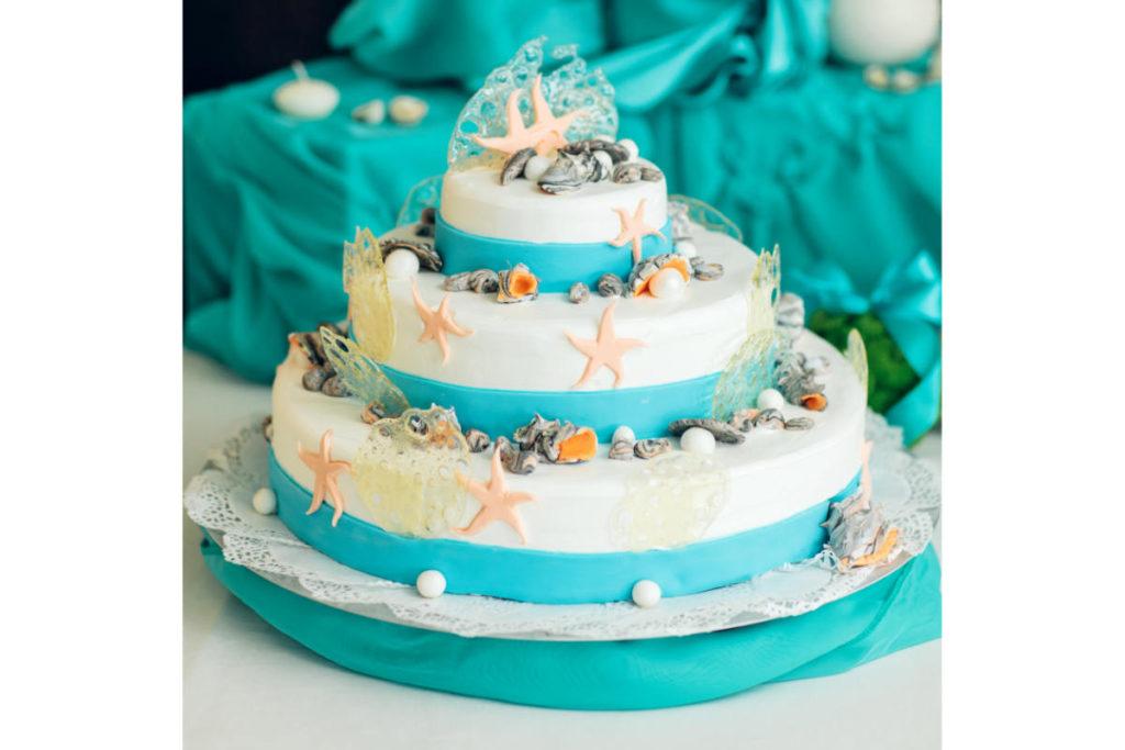 Dreistöckige Hochzeitstorte in Türkisfarben mit einem nautischen Motto dekoriert